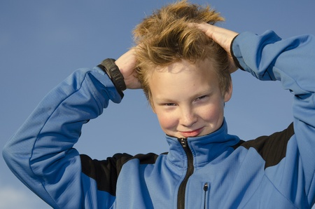 Kid adjusts his spiky hairstyle against blue sky background