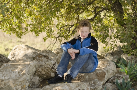 Boy sitting in nature on a rock under a tree Stock Photo - 17018467
