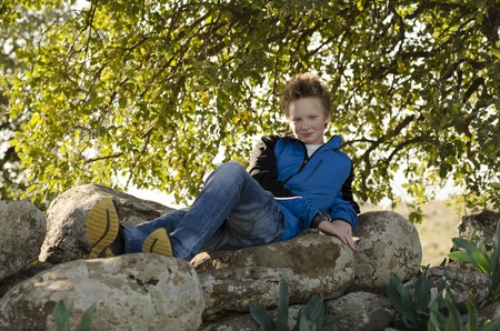 Guy resting in nature on a rock under a tree Stock Photo - 17018468