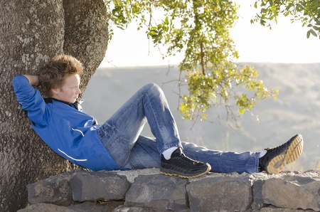 Teenager sitting on a rock under a tree Stock Photo - 17018465