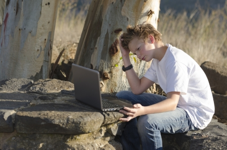 Thoughtful teenager sits on nature with laptop Stock Photo - 17018464