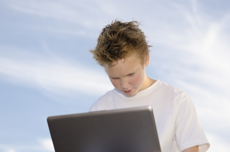 Thoughtful teen work on a computer through the wireless network Stock Photo - 17018461