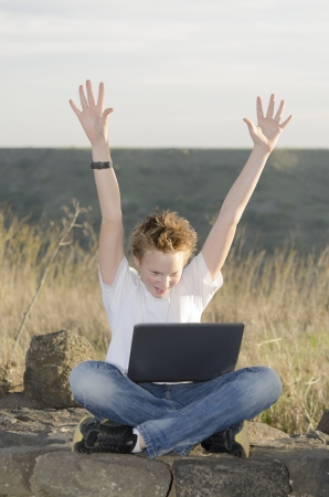 Shaggy teen with laptop joyously throws his hands up in nature