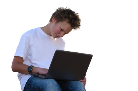 Pretty schoolboy with spiky hair work on mobile computer (isolated on white) Stock Photo - 17018478