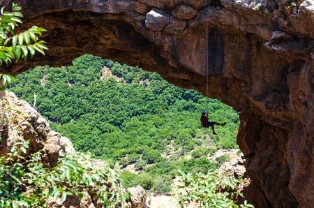 abseiling: Man descends down a natural rock bridge  Rainbow Keshet Cave Bridge, Israel