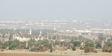 ceasefire: Syrian flag over destroyed and abandoned city of Quneitra in Syria Editorial
