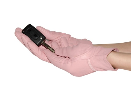 Key from new car in graceful hands in leather pink gloves isolated on white