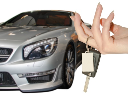 Elegant female hand holding car keys against expensive premium class auto