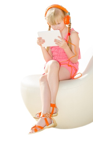 Girl in design armchair holding tablet PC and watching video in orange headphones isolated on white photo