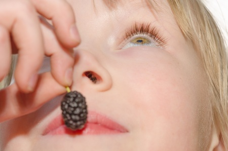 Closeup portrait of cheerful girl, holding in hand and eating mulberry fruit photo