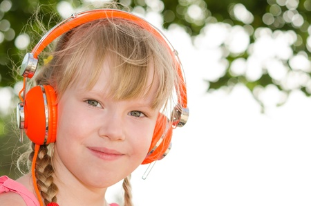 Closeup portrait of cheerful girl listening lesson in headphones against white green bokeh background photo