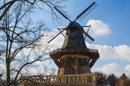 Traditionele oude Europese windmil bij de lente of de herfst bos landschap tegen blauwe hemel