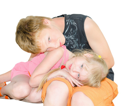 Two kids brother and sister curled up together isolated on white