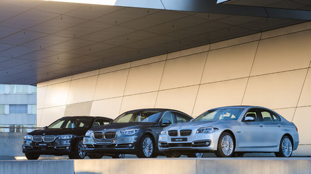 MUNICH, GERMANY - DECEMBER 27, 2013: New collection of powerful BMW 535 business and family classes. Three wet after rain cars - the entire model line: sedan, liftback, station wagon.
