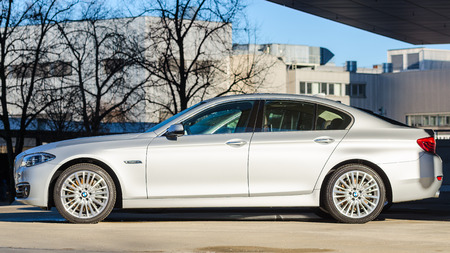 presti: MONACHIUM, Niemcy - 27 grudnia 2013: Boczne nowego modelu BMW 535i nowoczesny sedan. Mokre po deszczu prestiż samochodów biznes klasy.