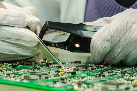 Mujer en guantes antiestáticos sosteniendo pincette y lupa reparación de componentes electrónicos en un circuito impreso