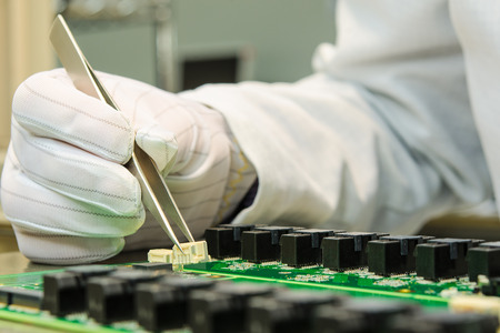 electronics parts: Female hand holding tweezers and installing connector on PCB in turnkey solutions high-tech manufacturing Stock Photo