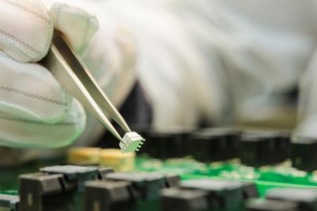 Mano femenina en los guantes de la celebración de pinzas ESD y montaje de microchip blanco sobre placa de circuito impreso