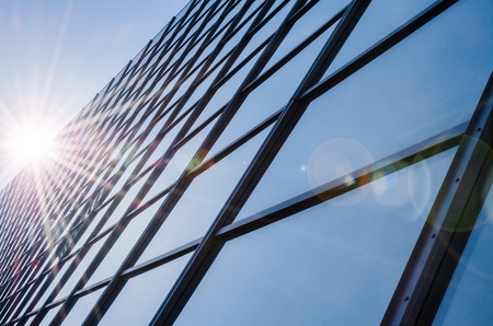 Glass and steel - mirrored facade of modern office building with sunbeams glare reflection