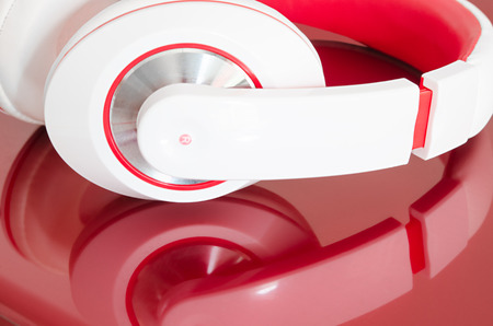 bordo: Red and white colorful headphones on bordo laptop mirrored surface Stock Photo