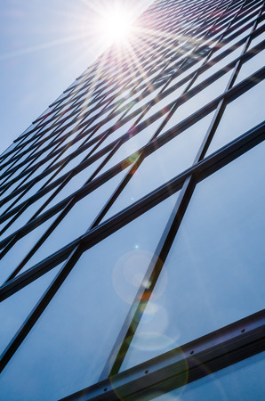 mirrored: Steel and glass - mirrored facade of modern skyscraper with glare reflection Stock Photo