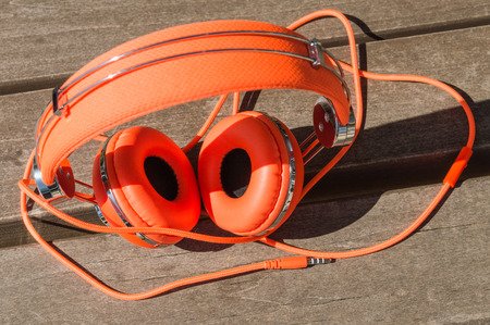 Vibrant orange wired headphones on the wooden bench