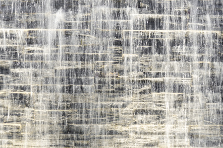 Flowing water over dark grey stone wall with spot backlight Standard-Bild