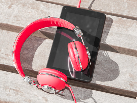 Red colored headphones and tablet PC for distance education or language course learning