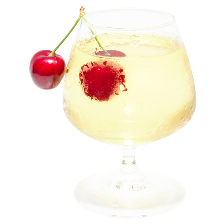misted: Misted wineglass full of cold white wine with dew drops and isolated ripe red cherry berry pair