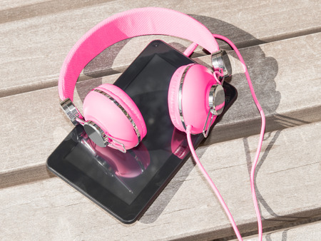 Female pink headphones and tablet pc for distance education and mobile leisure outdoors on wooden bench in park Stockfoto