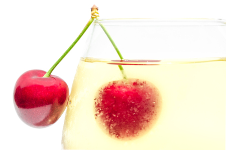 misted: Pair ripe cherry berries on top edge of full misted wineglass with cold white wine isolated close-up