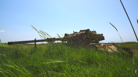 israel war: Old Israeli tank in the tall grass against blue sky  HDR photo  Stock Photo