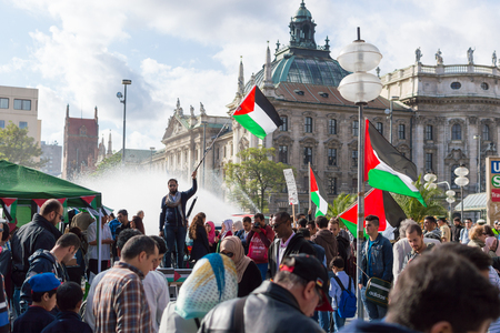 pleas: MUNICH, GERMANY - AUGUST 16, 2014: Anti-war meeting action in Europe. Pro-Palestinian activists calls from European Union government to take an active part in solving the Palestinian-Israeli conflict.