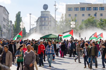 MUNICH, GERMANY - AUGUST 16, 2014: Pacific meeting against the rights infringement of the Palestinian population in Gaza, occupied of Israeli military forces. Activists with flags and slogans call for independence and freedom.