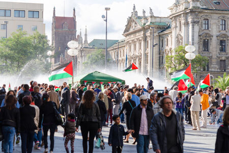 MUNICH, GERMANY - AUGUST 16, 2014: Palestinian demonstration in the center of a major European city. Activists with flags require a peaceful solution to the Arab-Israeli conflict and stop the bombing of Gaza.