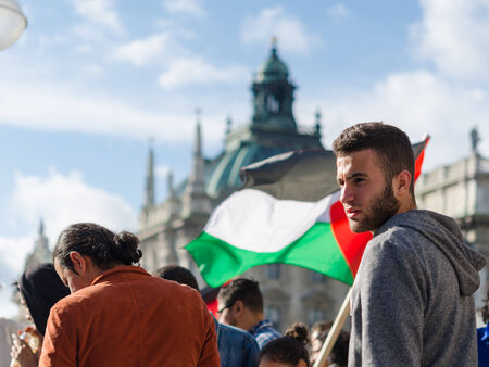 pleas: MUNICH, GERMANY - AUGUST 16, 2014: Face of a young activist on the background of the Palestinian flag. Pacific demonstration in support of the Gaza Strip population. For peace, freedom, independence and against a war. Editorial