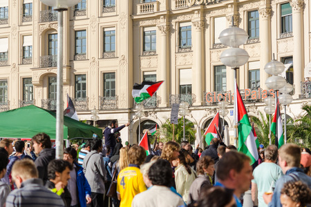 pleas: MUNICH, GERMANY - AUGUST 16, 2014: Palestinian flags over the German city. Anti-war rally demanding an end to the bombing of Gaza and the withdrawal of Israeli troops from Palestine.