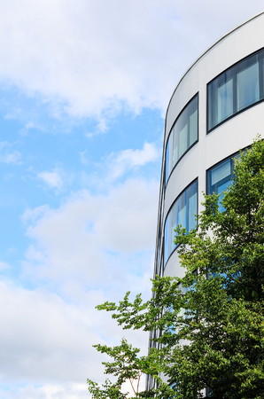 Modern office building mirrored windows and tree against blue sky as background with copy-space free place for text