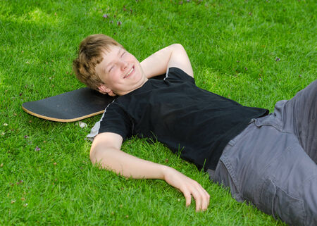 Laughing guy relax on skateboard in park grass and rest after an active leisure