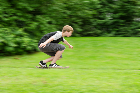 Young teen guy fast rides a skateboard in park. Slow shutter photo in action with blurred trees and grass background and copy-space place. photo