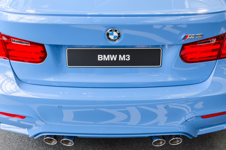 prestigious: MUNICH, GERMANY - AUGUST 9, 2014: Rear view of new generation model BMW M3 - prestigious sports style car. Close-up details with chrome exhaust pipes and stop lights.