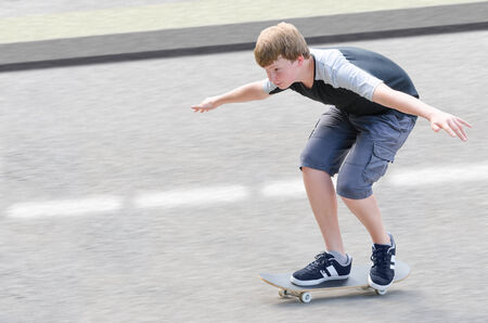 Young skater teenager guy in motion moving on skateboard along roadway against blurry asphalt background with copy-space area for text