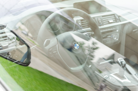 MUNICH, GERMANY - AUGUST 9, 2014: Interior of new modern model BMW car through the side window glass with grass reflection