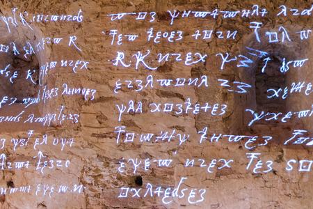 Gloeiende antieke runes karakters en brieven van woorden uit vurige tekst van de oude geschriften over de ruwe stenen muur Stockfoto