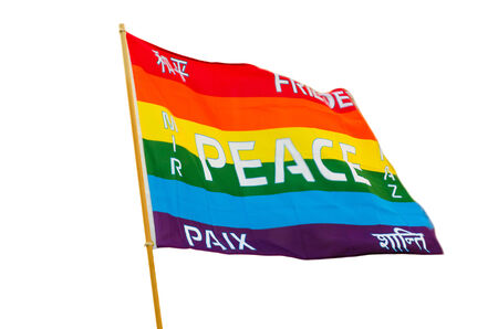 fluttering: Waving rainbow varicolored pacifist flag with multilingual peace text wind fluttering isolated on white background