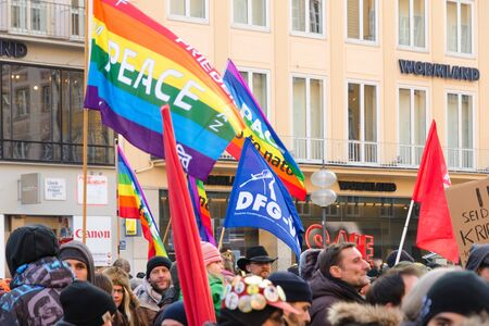 anti nato: Munich, Germany - February 07, 2015: European peaceful march with flags, placards and banners on central street