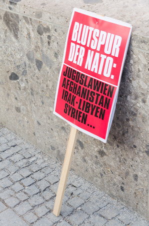 north atlantic treaty organization: Munich, Germany - February 07, 2015: Protest sign placard of anti-NATO rally demonstration against NATO expansion and increased presence of North Atlantic Alliance in Europe