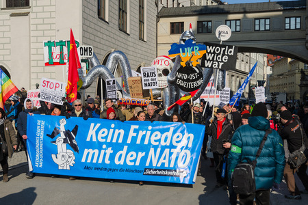 Munich, Germany - February 7, 2015: European anti-NATO peaceful protest demonstration. Texts on banners and placards says: Stop North Atlantic Alliance eastward expansion, No friendship with NATO. Editorial