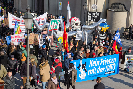 incursion: Munich, Germany - February 7, 2015: NATO in Europe like an octopus. Peaceful demonstration anti-NATO pacific protest rally. Text on the banner reads as No friendship with NATO. Editorial