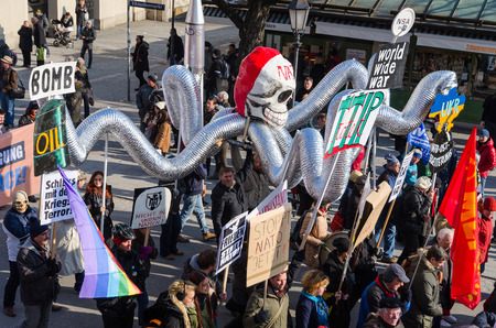 pacifism: Munich, Germany - February 7, 2015: Antiwar march procession against expansion of presence North Atlantic Alliance in Europe. Protesters and activists are bearing dummy of octopus with NATO skull.